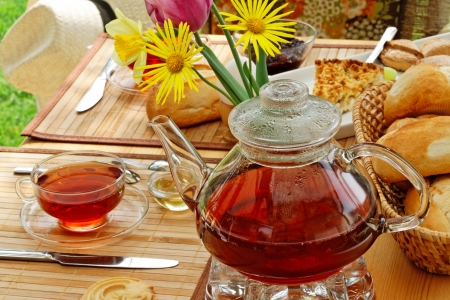 breakfast garden: Tea and simple food on a wooden table in the garden