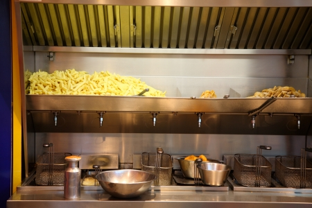 fryer: Chips production at a French fries stand. Stock Photo