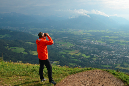 Man with orange jacket and triedr looking around countryside  G