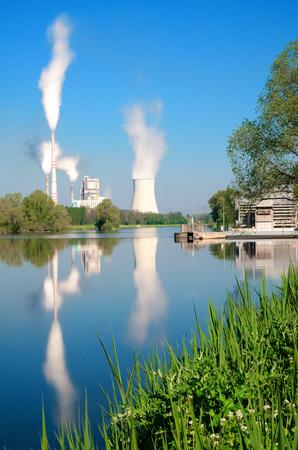 Grote thermische krachtcentrale met afspiegeling van de rivier