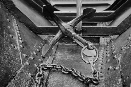 ship anchor: Old metalic, riveted ship with anchor on chain