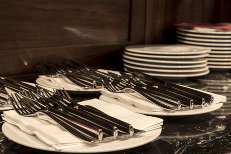 Plates with knifes and forks on the wooden credence Stock Photo