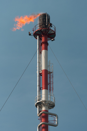 Chemical chimney with fire on the top, refinery, Slovakia