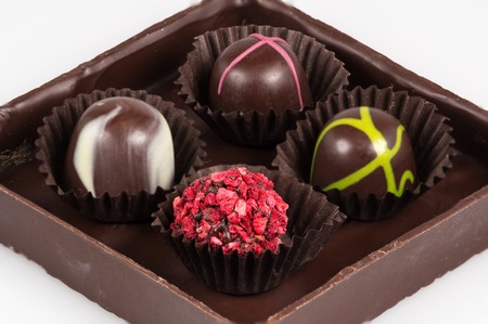 Chocolate composition with white background. Four chocolate bon-bons. Czech Republic