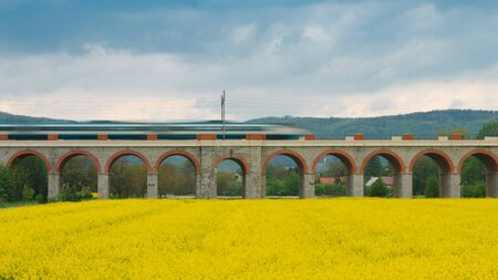 Historical railway bridge with fast train and cloudy sky