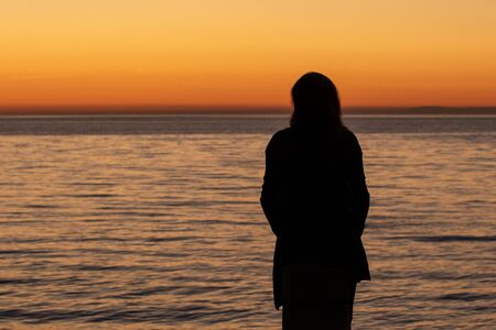 Woman is watching sunset on the beach