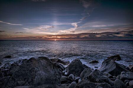 Beautiful sunrays above the atlantic ocean with stones, ACORES Фото со стока