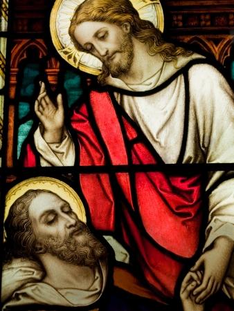 Gebrandschilderd glas in katholieke kerk tonen van Christus heling van een zieke man