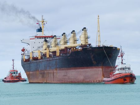 Two tugboats assisting huge vessel Stock Photo