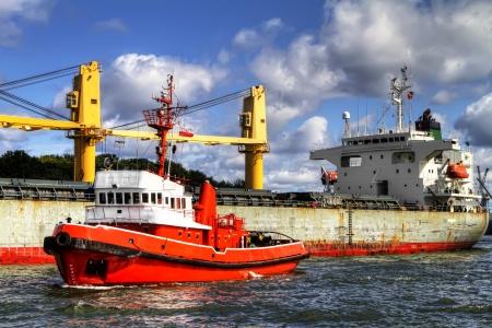 tug boat: A huge tugboat assisting huge vessel lto leave port