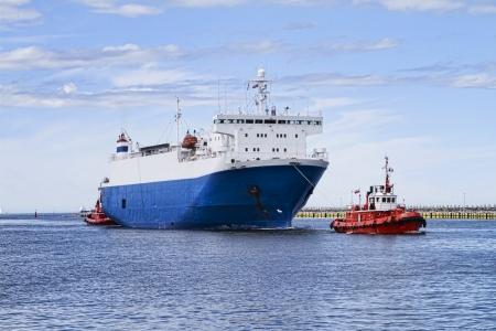 Twee sleepboten slepen enorme schip Stockfoto