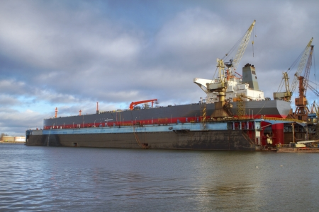 shiprepair: A hull of a ship is being renovated in a dry dock