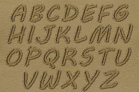 carved letters: English alphabet written on a beach sand.