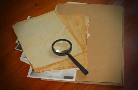 Vintage documents with magnifying glass investigation concept photo