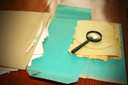 Vintage documents with magnifying glass investigation archives concept photo