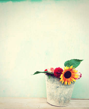Old boards with bucket of flowers vintage concept photo