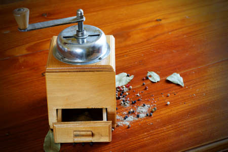 Old grinder background with pepper and allspice vintage table photo