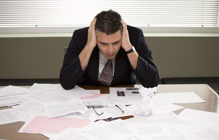 A businessman pondering over the paperwork