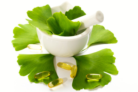 Healing leaves of ginkgo biloba tree in a white ceramic bowl and yellow capsules. Green leaves on a white background.