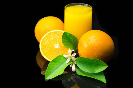 Oranges with green leaves and flowers. Orange juice in a glass cup. Still life with citrus fruit on a black background and with a dark reflection. Foto de archivo - 133571902