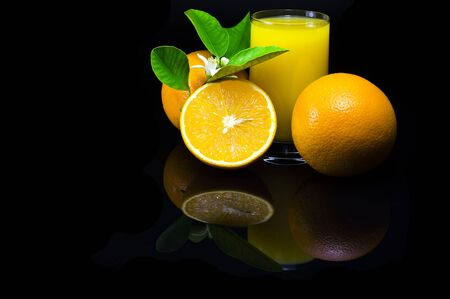Oranges with green leaves and flowers. Orange juice in a glass cup. Still life with citrus fruit on a black background and with a dark reflection. Foto de archivo - 133571903