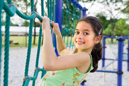Young girl enjoying the climbing rope activity in the playground Banque d'images
