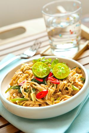 Plate of delicious stir fry chinese noodles with limes and chilis. photo