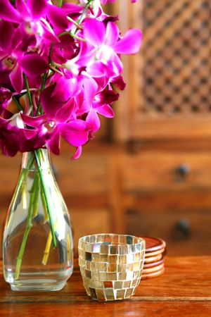 room accents: Vaso di orchidee fresche magenta su tavola in legno intagliato con mobili in stile indiano in background.