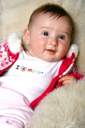 sheep skin: Cute baby girl on sheep skin rug. Stock Photo