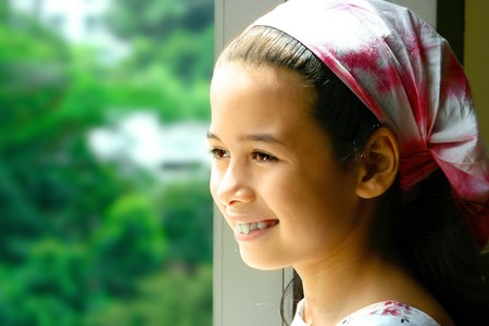 Pretty young girl in pink bandanna looking out into the nature's outdoor. Banque d'images