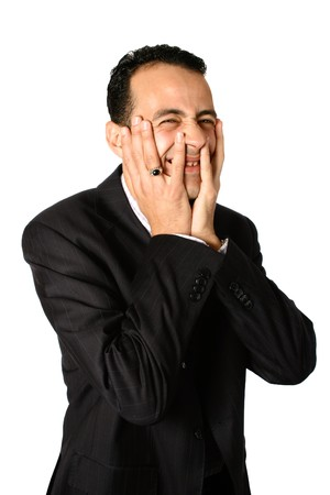 blunder: Young businessman with both palm covering half of his face, while grimacing in discomfort