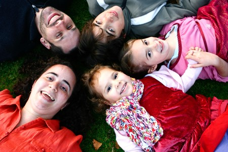Young happy family lying head to head on grass, outdoor, enjoying each other's company. Banque d'images