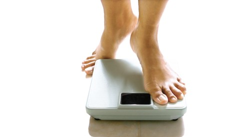 Pair of feminine feet about to stand on a weighing scale. Banque d'images