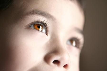 dilate: Closeup of beautiful brown eyes belonging to a child.