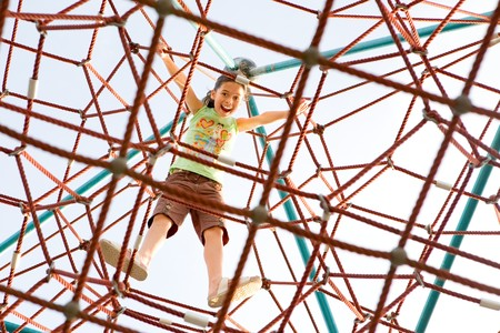 reached: Young girl excited that she has reached the top of the giant climbing web activity. Stock Photo