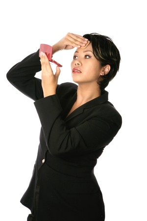 professionalism: Female Asian businesswoman touching up her makeup. Concept of presenting professionalism in corporate environment.