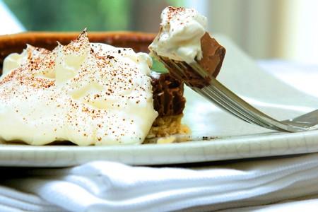 chuparse los dedos: Closeup gateux tarta de chocolate servido con nata fresca y polvo de cacao en polvo. Foto de archivo