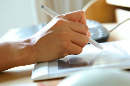 Hand holding stylus pen while working on tablet attached to computer. Stock Photo - 4522323