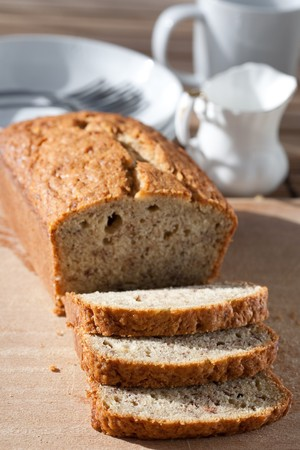 Delicious freshly baked banana bread on wooden board photo