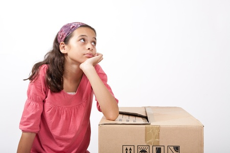 laborious: Lonely young girl feeling sad, resting on a cardboard box  Stock Photo