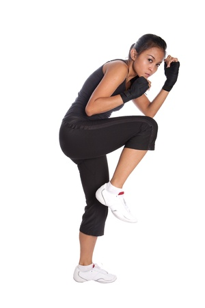 Female fitness trainer in fighting pose with one leg in air in self protect position. Banque d'images