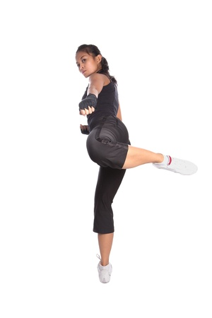 aerobic exercise: Female fitness trainer in fighting pose with one leg in air in side kick position.