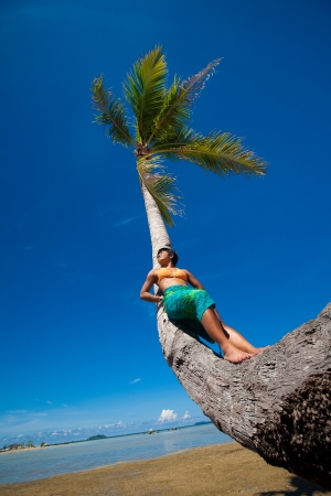 waterside: Young woman leaning against coconut tree by a tropical beach