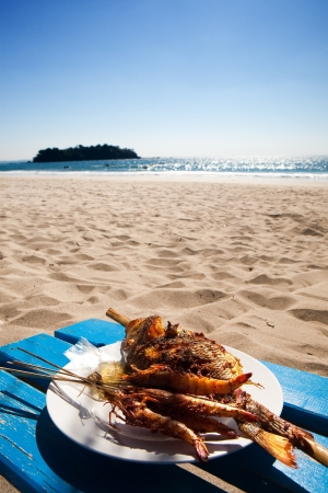 holiday food: Barbecued fish and prawns by a tropical beach