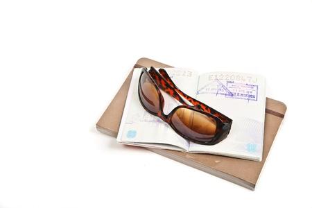 overseas visa: Journal, passport and sunglasses on white.