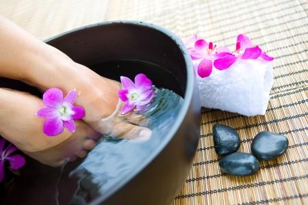 Weibliche Füße im Fußbad Schüssel mit Orchideen Standard-Bild