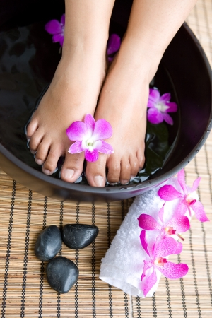 easing: Feminine feet in foot spa bowl with orchids