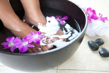 Feminine feet in foot spa bowl with orchids photo