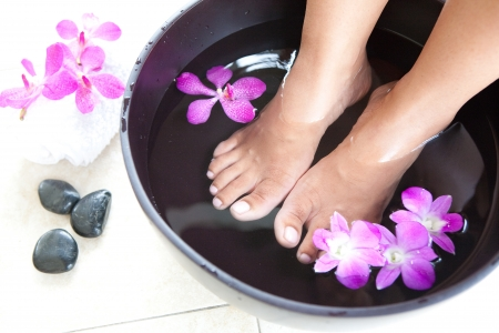 foot spa: Feminine feet in foot spa bowl with orchids