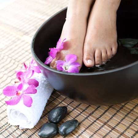 to soak: Feminine feet in foot spa bowl with orchids